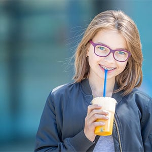 preteen girl with braces smiling holding drink